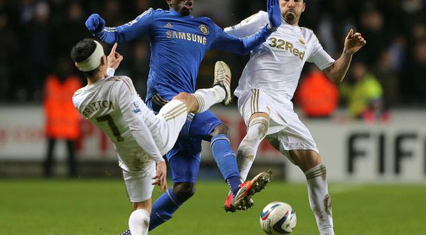 Chelsea's Demba Ba (centre) battles for the ball with Swansea City's Leon Britton and Chico (right) during the Capital One Cup, Semi Final, Second Leg match at the Liberty Stadium, Swansea. PRESS ASSOCIATION Photo. Picture date: Wednesday January 23, 2013. See PA story SOCCER Swansea. Photo credit should read: Nick Potts/PA Wire. RESTRICTIONS: Editorial use only. Maximum 45 images during a match. No video emulation or promotion as 'live'. No use in games, competitions, merchandise, betting or single club/player services. No use with unofficial audio, video, data, fixtures or club/league logos.