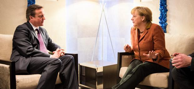 In this photo provided by the German Government Press Office (BPA), German Chancellor Angela Merkel (R) talks with British Prime Minister David Cameron at The World Economic Forum