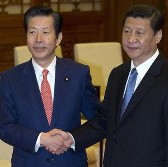 Japanese envoy Natsuo Yamaguchi, left, shakes hands with Chinese leader Xi Jinping in Beijing, China (AP)