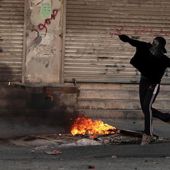 A Bahraini anti-government protester throws a stone toward riot police during clashes (AP)