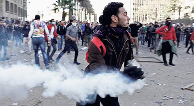 An Egyptian protester runs with a live tear gas canister during clashes with riot police in Cairo's Tahrir Square