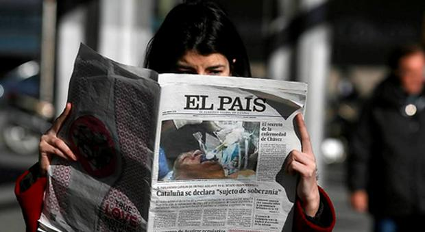 A woman holds a copy of Spanish newspaper 'El Pais'.