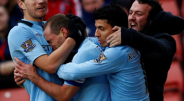 Manchester City's Pablo Zabaleta (2nd L) celebrates his goal against Stoke City with Edin Dzeko (L) Sergio Aguero (2nd R) and a fan during their FA Cup fourth round soccer match at the Britannia Stadium in Stoke-on-Trent, northern England, January 26, 2013. REUTERS/Darren Staples (BRITAIN - Tags: SPORT SOCCER)