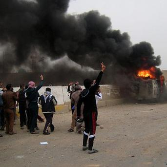 Protesters chant slogans against Iraq's Shiite-led government near a burning Iraqi army vehicle Fallujah (AP)
