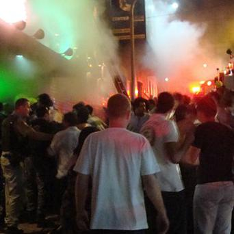A crowd stands outside the Kiss nightclub while a fire burns inside the club in Santa Maria city, Rio Grande do Sul state, Brazil (AP)