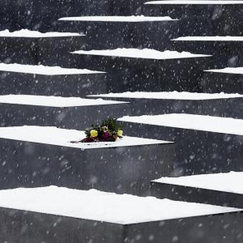Flowers on a slab of the Holocaust Memorial to commemorate the victims of the Nazis at the International Holocaust Rememberance Day in Berlin (AP)