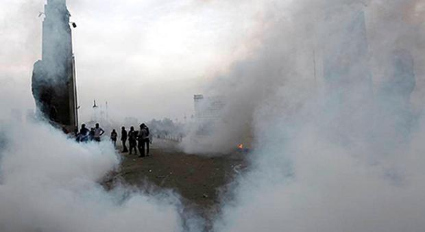 Protesters opposing Egyptian President Mursi are seen through tear gas fired by riot police during clashes in Cairo yesterday