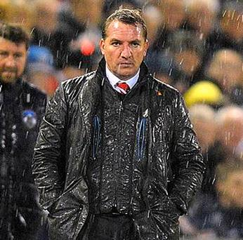 Liverpool manager Brendan Rodgers stands in the rain on the touchline during yesterday's match in Oldham
