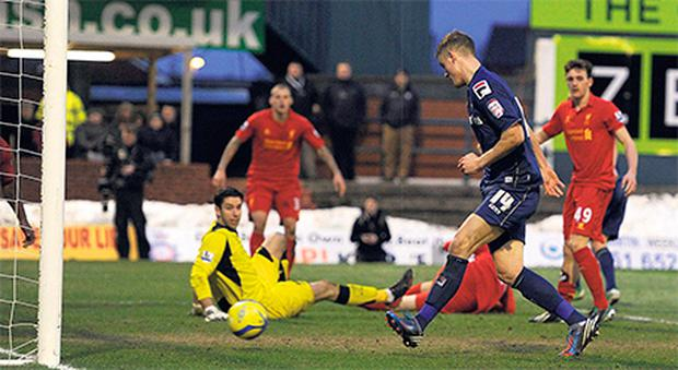 Liverpool goalkeeper Brad Jones is left down and out as Matt Smith scores Oldham's second goal