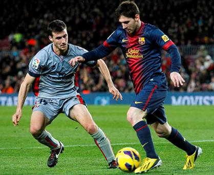 Barcelona's Lionel Messi (right) eludes Osasuna's Oier Sanjurjo during their Spanish First division soccer league match at Camp Nou stadium in Barcelona
