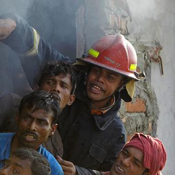 Bangladeshi firefighters and volunteers work to douse a fire at a clothing factory in Dhaka (AP)