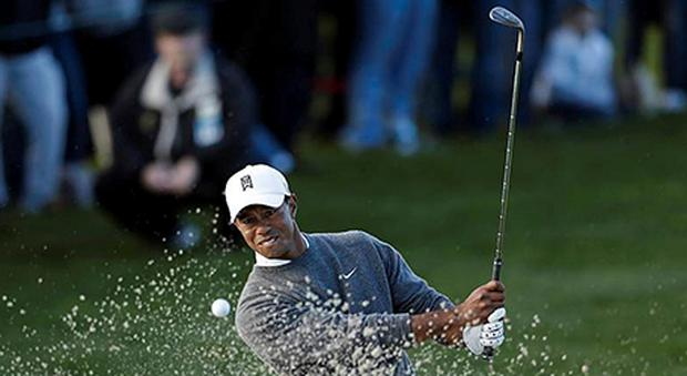 Tiger Woods hits out of a bunker on the fifth hole during the fourth round of the Farmers Insurance Open golf tournament in San Diego