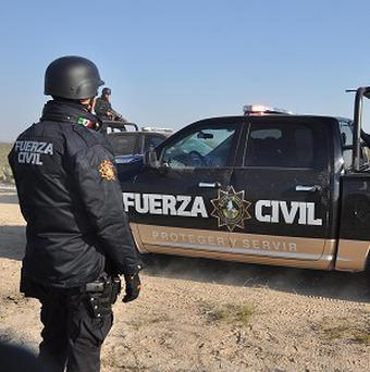 Nuevo Leon state police stand guard on a dirt road leading to a ranch near the town of Mina, in northern Mexico (AP)
