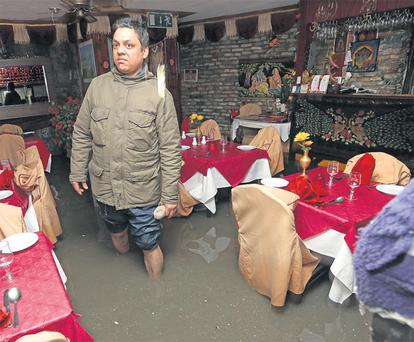 Sandeep Kumar inspects flood damage in Kumar's Indian Restaurant, Galway