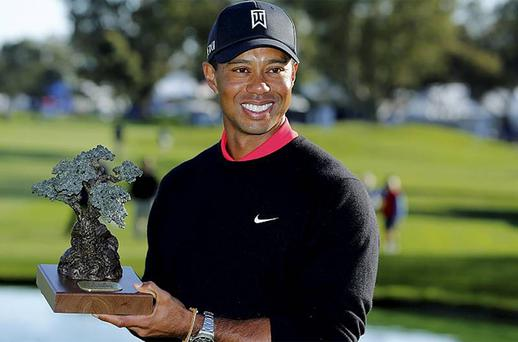 Tiger Woods holds the trophy after winning the Farmers Insurance Open in San Diego, California. Photo: Reuters