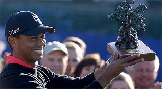 Tiger Woods holds the winner's trophy after his victory in the Farmers Insurance Open at Torrey Pines