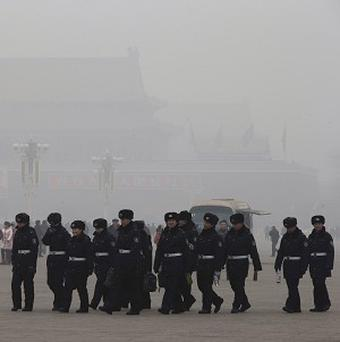 Chinese security personnel march across Tiananmen Square in a thick pollution haze in Beijing (AP)