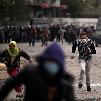 Egyptian protesters run for cover during clashes with riot police in Cairo (AP)