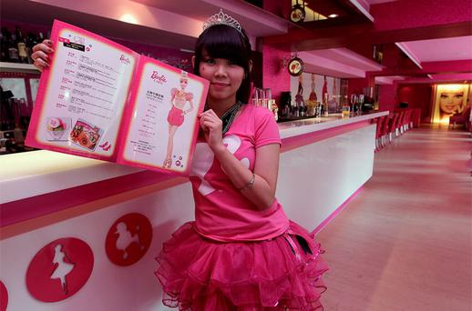 A waitress poses with a menu at a Barbie-themed cafe in Taipei. Photo: Reuters