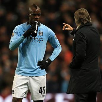 Roberto Mancini, left, says Mario Balotelli is like one of his children