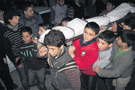 Children carry the body of a friend who was killed by shelling during heavy fighting between the Free Syrian Army and the forces of Syrian President Bashar al Assad in the Jobar district of Damascus. Photo: Reuters