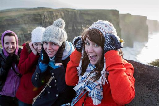 Australian tourists, from left, Lindsay Klassen, Melissa Klassen, Christie Hodge and Maddi Brick hang on to their hats at the famous Cliffs of Moher after the visitor centre was closed because of the stormy conditions