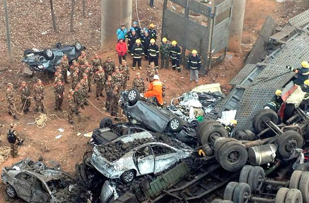 Rescuers look for survivors near a wreckage of vehicles after a expressway bridge partially collapsed on the Lianhuo highway in Mianchi county. Photo: Reuters