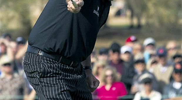Phil Mickelson watches his birdie putt roll towards the cup on the ninth green during first round of the Phoenix Open - Mickelson's putt lipped-out, and he had to settle for par on the hole and a round of 60