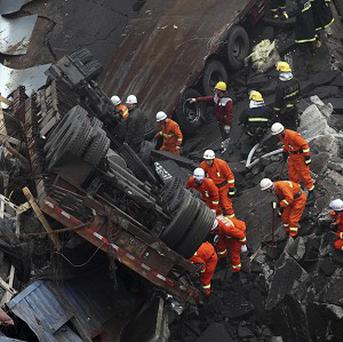 Rescuers work at the accident site where a motorway bridge partially collapsed due to a truck explosion in China (AP)