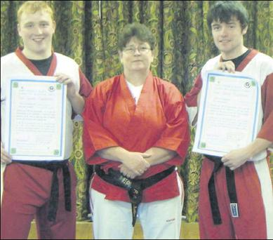 Daire Lawless and Philip Corway show off their First Dan Black Belt Certificates with Cobra Kan instructor Patricia McQuillan.