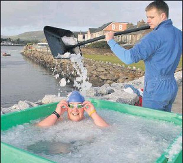 Stephen O'Neill of Ó Cathain Iasc Teo shovelling ice onto Dingle's Nuala Moore in preparation for her ice-swim. Credit: Photo by Marian O'flaherty