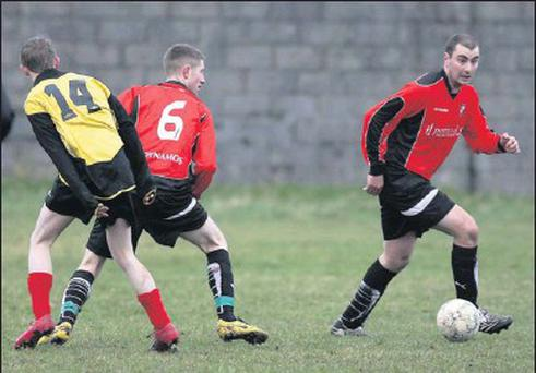 James Wall, Tralee Dynamos, defending with Scott Monaghan in support, as Shannon Wanderer attacker Brendan O'Gorman lurks during their Denny Division 1A game in Ballybunion on Sunday. Photos by John Reidy