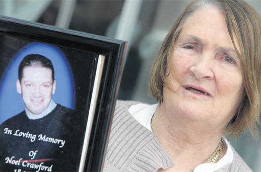 The victim's mother Mary Crawford is pictured outside court at a previous hearing with a picture of her late son Noel. Photo: Courtpix