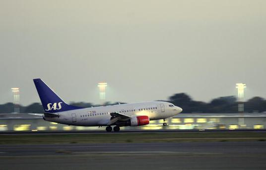 An SAS plane takes off at dusk from Tegel airport in Berlin, October 12, 2010 (Photo credit should read ODD ANDERSEN/AFP/Getty Images)