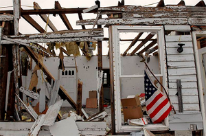 An American Flag hangs on the side of a tornado damaged house in Henryville, Indiana March 4, 2012. Photo: Reuters
