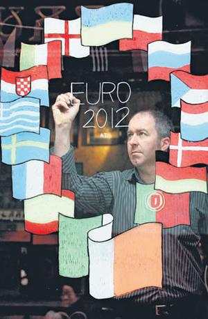 Andy Davies puts the finishing touches to a mural on the window of McDaids pub on Harry Street in Dublin city centre yesterday. Photo: MARK STEDMAN