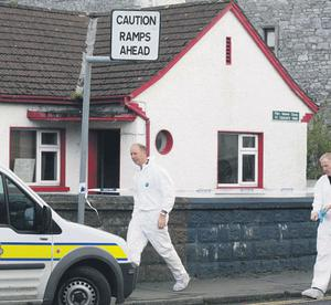 Garda forensic officers at the house in St Ciaran's Park, Roscommon town, where the three men were found dead