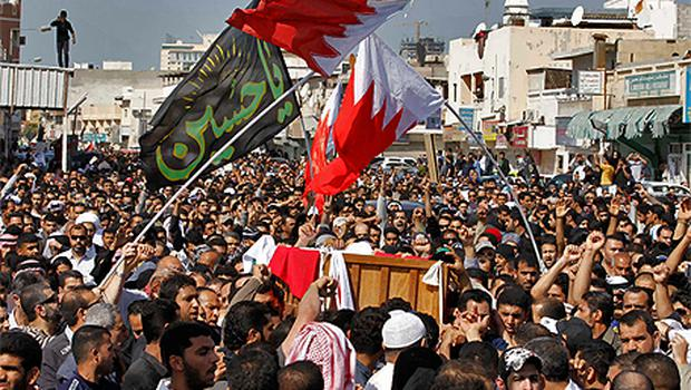 People carry the body of a demonstrator killed during a protest on Monday, as they gather at a Shi'ite village cemetery in Sanabis, west of the Bahraini capital Manama yesterday