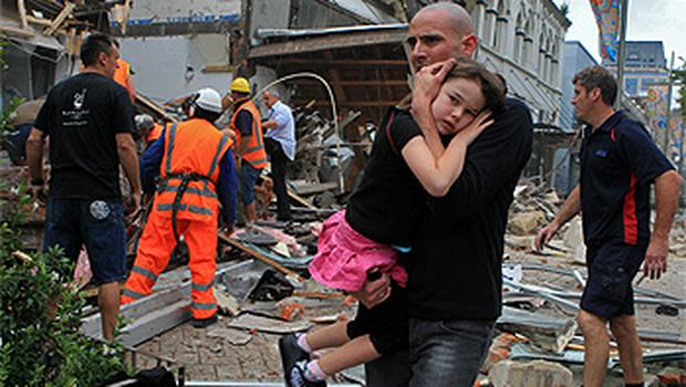 A man carries a child to safety in his arms following the earthquake in Christchurch. Photo: Reuters