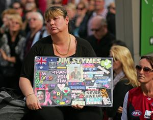 MELBOURNE, AUSTRALIA - MARCH 27:  A woman looks on as she watches the television broadcast outside of the State Funeral held for former AFL player Jim Stynes at St Paul's Cathedral on March 27, 2012 in Melbourne, Australia.  (Photo by Scott Barbour/Getty Images)