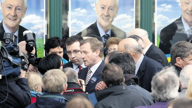 Enda Kenny on the campaign trail in Donegal yesterday, amid posters of veteran FG Donegal South West TD Dinny McGinley