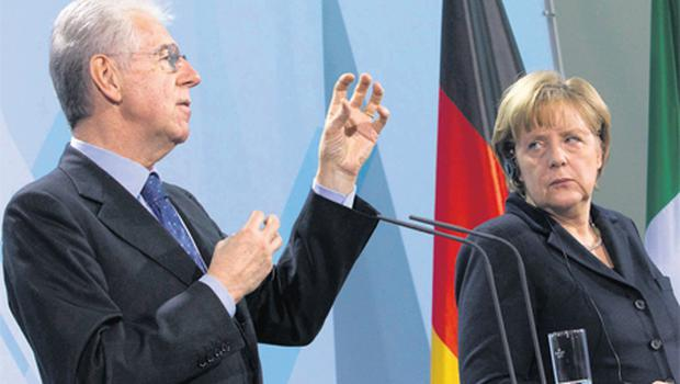 German Chancellor Angela Merkel listens to Italian Prime Minister Mario Monti during a news conference after talks at the Chancellery in Berlin yesterday