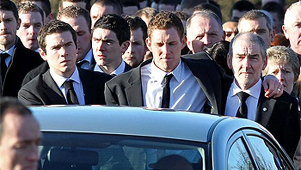 Matthew Harte, John McAreavey and Mickey Harte walk behind the hearse