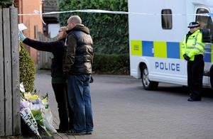Members of the public look at the tributes left at the police cordon. Photo: PA