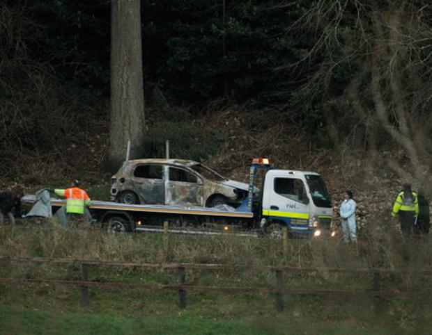 A burnt out car is removed from the scene at Ravensdale Park near Dundalk, in which two bodies were found. Niall Carson/PA Wire
