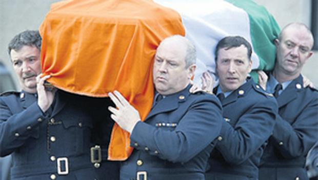 Garda colleagues carry the remains of Supt Dorney