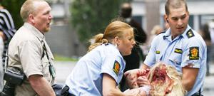 Police help a young victim of the bombing in Oslo yesterday. Photo: AP