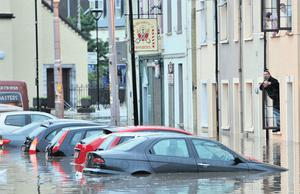 Residents of Blackpool in Cork City look out their windows after the heavy rains flooded the street