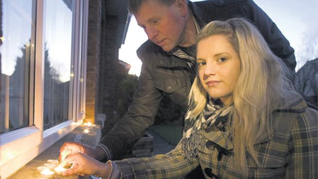 Meg's daughter Sasha Keating and brother James Walsh light candles outside the murdered mum's former home in Co Waterford to mark what would have been her 40th birthday