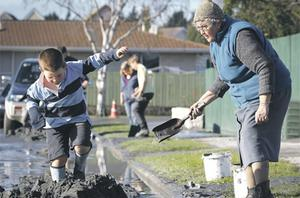 Elizabeth Parsons (73) looks on yesterday as her grandson plays in a pile of sludge, the day after two magnitude 6.0 and 5.5 earthquakes struck the quake-damaged city of Christchurch in New Zealand